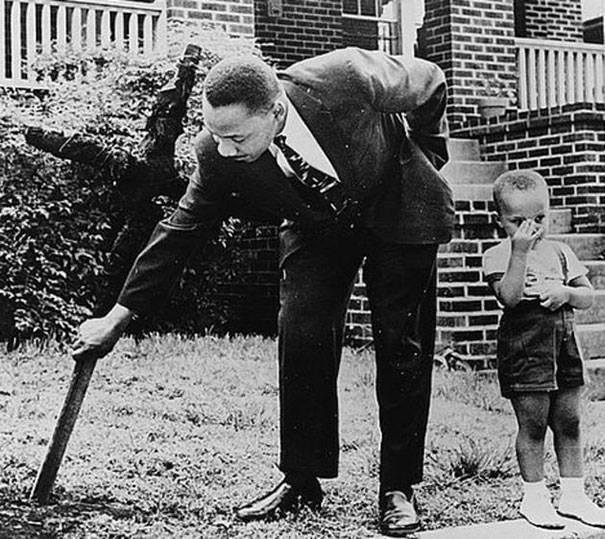 Martin Luther King and his son removing a burned cross that KKK members left in front of his house in 1960.