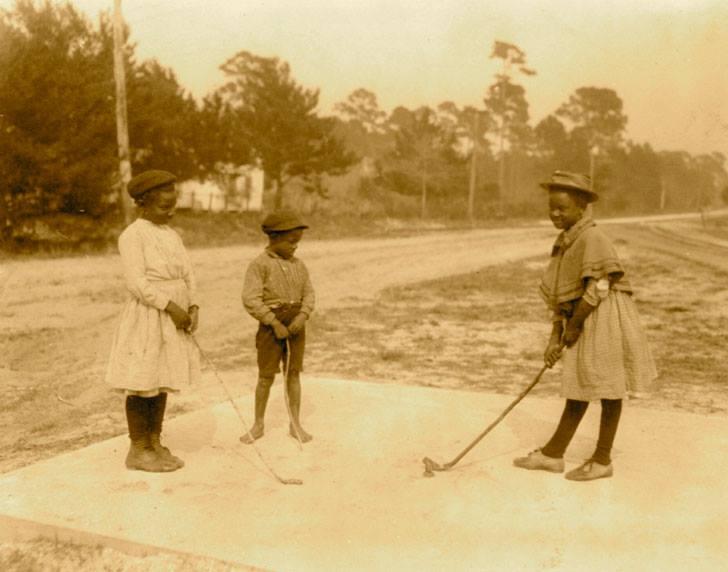 niños juegan al golf con palos hechos de madera