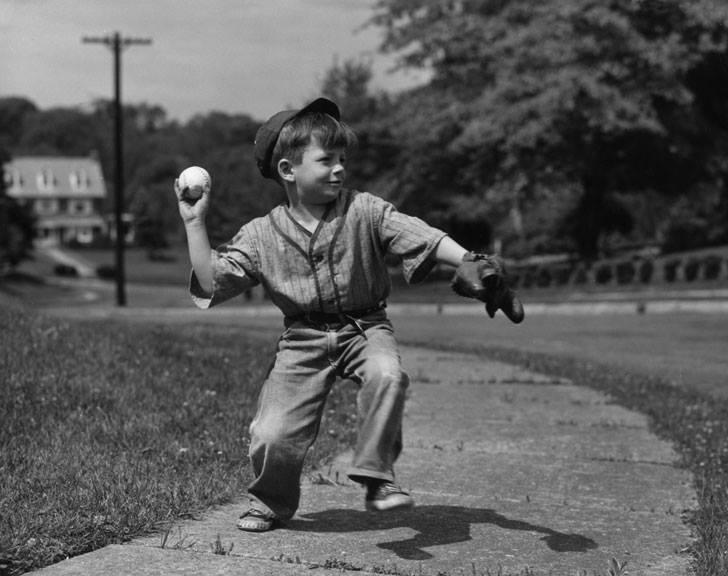 un niño lanza una pelota de béisbol en la calle