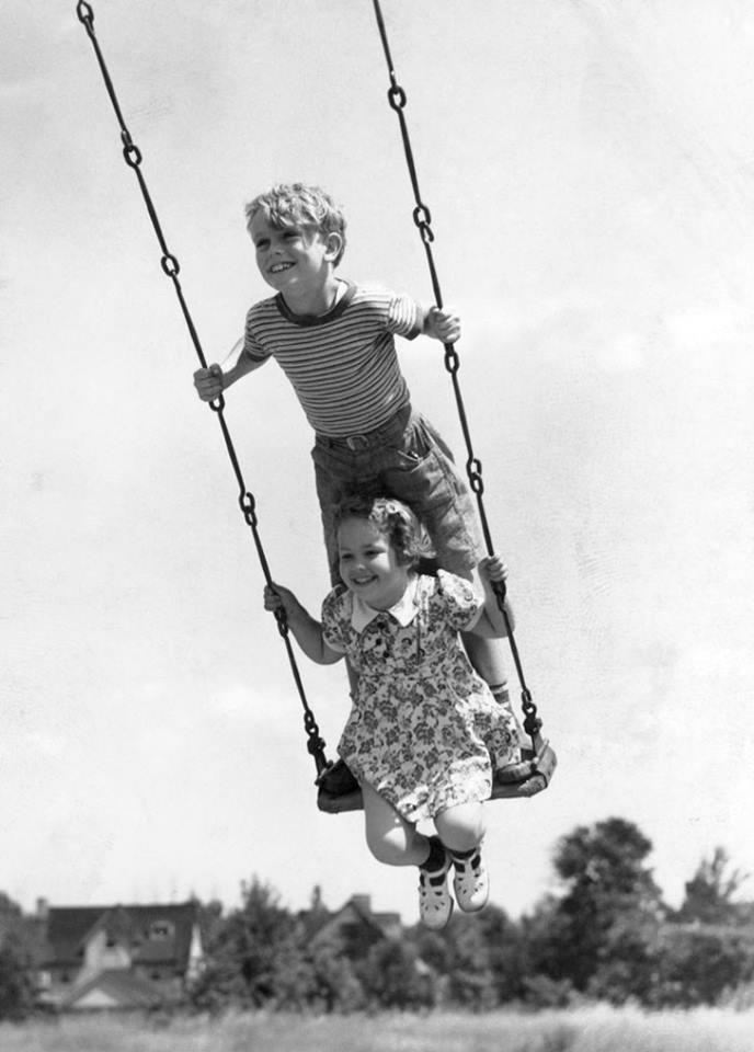 un niño y una niña sobre un columpio